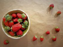 Background of strawberries for greetings and blessings: anniversaries, Valentine`s Day, birthdays, restaurant, love, friendship. Strawberries in a bowl and on stock photos