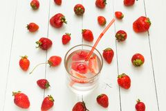 Background from strawberry water and fresh berries on a white table. Detox, a healthy lifestyle royalty free stock photography