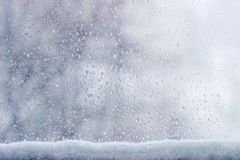 Background of the window pane during a sleet. Background of the streams and drops of water on the window pane with accumulation of wet snow at the bottom of Royalty Free Stock Photo
