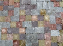 Street road stone paving of multicolor bricks. Background of street road colorful stone paving of multicolor bricks, close up, high angle view Stock Images