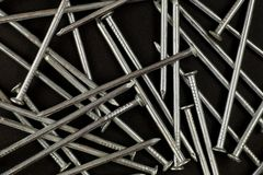 Background. A structure consisting of new shiny nails on a dark background stock photography
