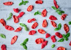 Background of sun dried tomato slices with basil leaves on concrete table Royalty Free Stock Photo