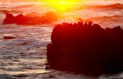 Background of sunset and waves crashing on rocky coastline near Monterey, California, USA. Dramatic sunset background of ocean waves on Asilomar State Marine Royalty Free Stock Photos
