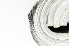 Background surface of few twisted magazines on white background with copy space royalty free stock photography
