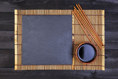 Background for sushi. Bamboo mat and soy sauce on black wooden table. Top view with copy space Stock Images