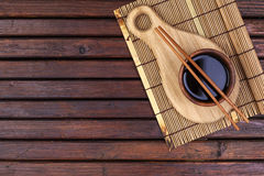 Background for sushi. Bamboo mat, soy sauce, chopsticks on wooden table. Top view and copy space stock photo
