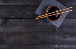 Background for sushi. Soy sauce, chopsticks on black stone. Top view with copy space Royalty Free Stock Image