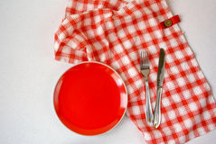 Background - table with red plate. Background: white textured surface of the table, a tablecloth on it in red cell red plate Stock Images