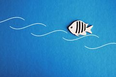 Background for text is a small fish in the waves in blue water royalty free stock photo