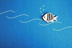 Background for text is a small fish in the waves in blue water stock images