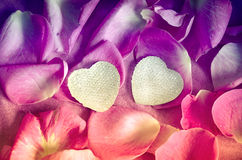 Background texture of beautiful pink rose petals and two hearts. The concept of love and romance. Valentines Day decor. Royalty Free Stock Photos