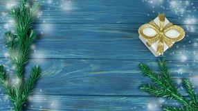 Background texture of blue with branches of a Christmas tree. And a decor of a gift box of gold color with a bow Royalty Free Stock Photo