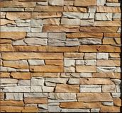 Background and texture. Brown and gray wall made of embossed natural stones blocks.  royalty free stock photography