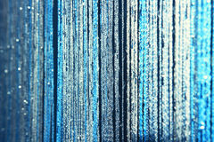 Background texture curtains made of blue threads with glitter and blur at the edges. Fibers of threads of blue curtains sparkle in the light Stock Photo