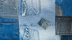 Background texture of denim fabric with pockets and stitched seams with buttons and rivets from different pieces of jeans Royalty Free Stock Photos