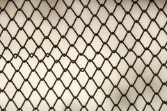 Background and texture for design. Abstract chain link fence texture against grungy gray color wall. Stock Image