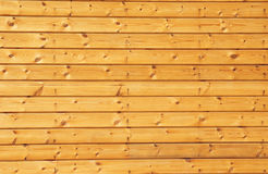 Background texture of finely slatted natural brown pine wood on the new house facade wall Royalty Free Stock Images