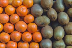 Background texture fruits of kiwi and mandarins. Background texture of folded kiwi fruits and tangerines on the market counter Royalty Free Stock Photo