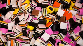 Background texture of liquorice allsorts. Background texture of multicolored liquorice allsorts candy with a variety of shapes and colors giving a random pattern Royalty Free Stock Images
