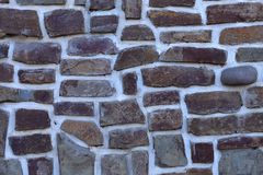 Background texture of masonry walls made of natural stone of different shapes and colors. stock images