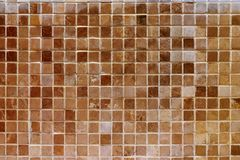 Old brown mosaic wall. Background texture of old brown mosaic on the wall Stock Images