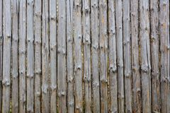 Background texture of old grey wooden fence from whole logs with  knots. Shabby fence royalty free stock photography