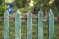 Background texture of old painted green paint wooden fence in the village. Cropped shot, horizontal, place for text, without people. Concept of construction stock photography