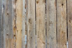 Grey wooden fence, old wooden fence made of old boards. Background, texture of old wooden planks, old rustic fence with slits between Stock Image