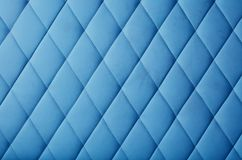 Blue leather upholstery background texture. Background texture of pastel blue genuine leather soft tufted furniture or wall panel upholstery with deep diamond stock image