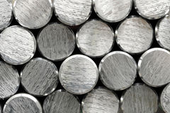 Background texture and pattern of aluminium bars. With focus to the cut and bevelled ends of the round metallic silver rods in a full frame view stock photography