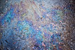 Texture of a petrol spill on asphalt road. Background texture of a petrol spill on asphalt road royalty free stock photo