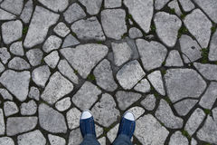 Background, texture of rough stone on the pavement. The legs in the sneakers are a top view Stock Photo