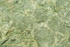 Background, texture - rough surface of cliff from serpentinite. Natural stone with a green tint Stock Images