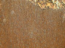 Background texture of rust. Metal sheet of red and orange color, covered with rust. The remains of the old paint remained in the corner. Rough texture stock photography