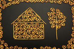 Background texture of salted pretzels and mini sticks in the shape of a house and a tree on a black background.  stock photos