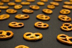 Background texture of salted savory mini pretzels in the traditional looped knot shape on the black background. Perspective royalty free stock image