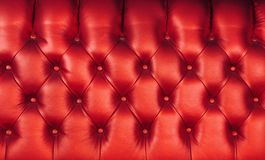 Red leather capitone background texture. Background texture of scarlet red capitone genuine leather, retro Chesterfield style soft tufted furniture upholstery royalty free stock images