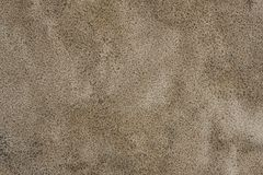 A background texture of unrefined, damp and grainy natural golden sand. royalty free stock image