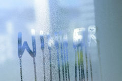 Background texture of water droplets in clear window glass surface. With Winter text Royalty Free Stock Images