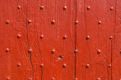 Background texture weathered red wooden door with nail decoration Royalty Free Stock Image
