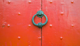 Background texture weathered red wooden door with nail decoration and iron circular door knocker Royalty Free Stock Images