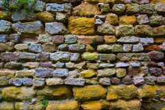 Background texture of a weathered rough stone wall. Background texture and pattern of a weathered rough stone wall with rough hewn rectangular blocks in rows in Royalty Free Stock Photo