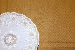 Background and texture of a white openwork round napkin on a bei Stock Image