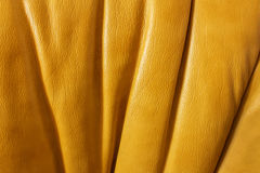 Background textured leather. Rich orange color with pleats Royalty Free Stock Photos