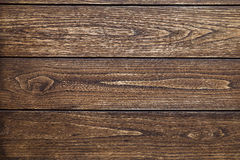 Background of three horizontal boards of dark wood with knots and traces of processing Stock Image