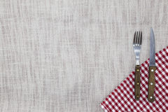 The background to create the restaurant`s menu. Linen tablecloth fork knife on a bright checkered cloth. Is used to create a menu Royalty Free Stock Images