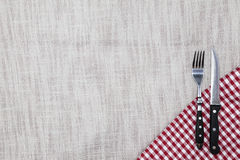 The background to create the restaurant`s menu. Linen tablecloth fork knife on a bright checkered cloth. Is used to create a menu Stock Image
