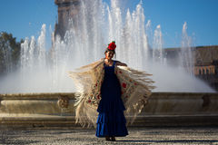 The happy woman dancing flamenco near the fountain. Dancing flamenco on a spring day royalty free stock images