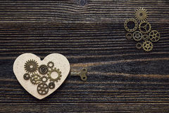 Background to the shape of hearts, the gear mechanism and a key. On a dark wooden table. Valentine`s Day concept. Space for text. Top view Stock Photography