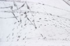 Traces of tires and footprints of shoe sole on snow Royalty Free Stock Image